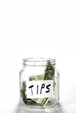 Tips Money Jar With Dollars. Glass money jar labeled tips has a few dollar bills in it Royalty Free Stock Images