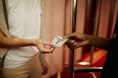Tips for porter. Hotel guest giving porter money for carrying her baggage Stock Photo