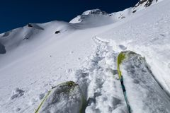 Tips of touring skis following track towards mountain pass Stock Photo