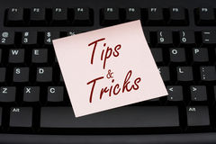 Tips and Tricks. Computer keyboard with a pink sticky note with text tips and tricks, Tips and Tricks royalty free stock image