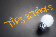 Tips and Tricks. Handwriting on chalkboard with glowing light bulb royalty free stock photos