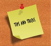 TIPS AND TRICKS handwritten on yellow sticky paper note over cork noticeboard background. Stock Image