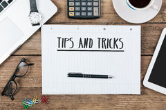 Tips, tricks on notebook on Office desk with computer technology. Words tips, tricks on notebook, Office desk with electronic devices, computer and paper, wood royalty free stock photography