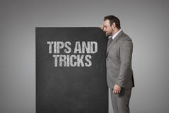 Tips and tricks text on blackboard with businessman Royalty Free Stock Images