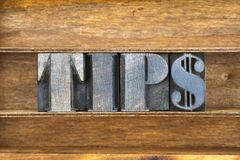Tips word tray. Tips word made from wooden letterpress type inside tray with dollar sign Stock Photo