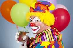 Tipsy Clown Sneaks a Drink. Alcoholic clown sneaks a drink from his flask Stock Image