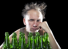 Tipsy man sits with a heap of beer bottles, a hangover Royalty Free Stock Photos