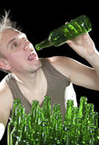Tipsy man wants to drink the last drink of beer from an empty bottle Stock Images