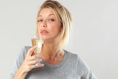 Tipsy young blond woman drinking bubbly wine. Female drinker - tipsy young blond woman drinking a flute of bubbly wine suffering from booze addiction, gray stock photography