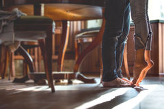 Tiptoe love. Happy barefoot couple at the kitchen, girl standing on tiptoe try to kiss husband Royalty Free Stock Images