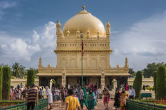 Tipu Sultan Mausoleum, Mysore, India. Mysore, India - October 26, 2013: Cream yellow Tipu Sultan mausoleum with dome under heavy cloudscape. People walking to Stock Photos