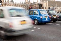 Tipycal London fährt die Aufwartung durch die Ampel vor uns mit einem Taxi stockfotografie