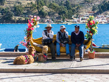 Tiquina, Βολιβία - 7 Δεκεμβρίου 2011: Τρία άτομα που κάθονται σε έναν πάγκο Στοκ Εικόνα