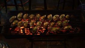 Tiré d'un processus de faire cuire des fruits de mer sur un barbecue sur un marché asiatique de nuit banque de vidéos
