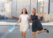 Tiré de deux jeunes amis féminins ayant l'amusement tout en faisant des emplettes Photographie stock
