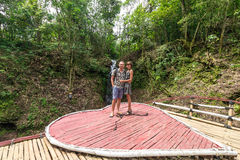 Tiré de jeunes couples affectueux de lune de miel se tenant ensemble dans des couples de forêt tropicale dans l'amour se tenant p Image stock
