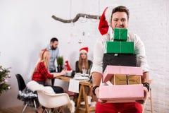 Tiré des amis heureux appréciant des vacances Concentrez sur l'homme avec les boîte-cadeau dans le premier plan dans un chapeau r Images libres de droits