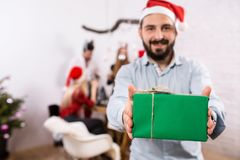 Tiré des amis heureux appréciant des vacances Concentrez sur l'homme dans le premier plan dans un chapeau rouge de Noël Image libre de droits