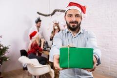 Tiré des amis heureux appréciant des vacances Concentrez sur l'homme dans le premier plan dans un chapeau rouge de Noël Photo libre de droits