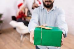 Tiré des amis heureux appréciant des vacances Concentrez sur un cadeau dans des mains de l'homme dans le premier plan Image stock