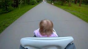 Tiré du point de vue de l'homme marchant une poussette avec le bébé clips vidéos