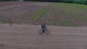 Tiré par derrière, l'appareil-photo suit l'homme sur la bicyclette faisant un cycle sur le chemin de terre au coucher du soleil banque de vidéos