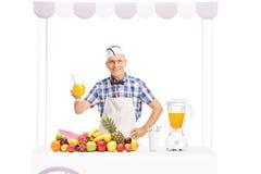 Tirón de soda maduro que sostiene un vidrio de zumo de naranja Foto de archivo libre de regalías