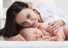 Tir étroit d'une mère touchant son bébé nouveau-né de sommeil Photographie stock