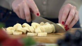 Tir étroit de couper en tranches la banane dans les morceaux minuscules banque de vidéos