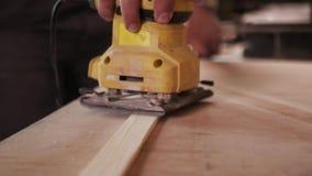 Tir étroit panoramique du processus de meulage manuel dans la main du charpentier clips vidéos