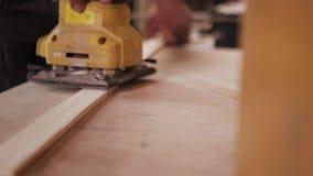 Tir étroit panoramique du processus de meulage manuel dans la main du charpentier banque de vidéos