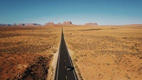 Tir aérien étonnant de la conduite argentée le long de la route américaine étonnante de route de désert de grès en vallée de monu banque de vidéos