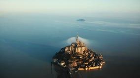 Tir aérien cinématographique du château éthéré d'île de Mont Saint Michel de lever de soleil entouré par la mer de marée haute en clips vidéos