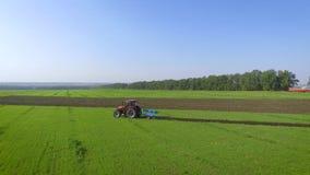 Tir aérien d'arc du fonctionnement rouge de tracteur sur le champ vert labourant le sol banque de vidéos