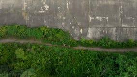 Tir aérien d'un jeune homme et de son fils courant au territoire d'une vieille 1ère forteresse de guerre mondiale pendant le couc banque de vidéos