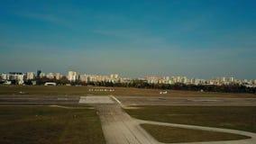 Tir aérien d'un petit atterrissage d'avion de propulseur sur la piste d'aéroport de ville un jour ensoleillé Photos stock