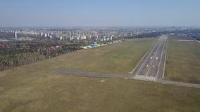 Tir aérien d'un petit avion de propulseur volant près de la piste d'aéroport de ville un jour ensoleillé Photos stock