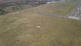 Tir aérien d'un petit avion de propulseur volant près de la piste d'aéroport de ville un jour ensoleillé Images stock