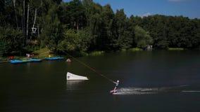 Tir aérien d'une benne suspendue dans un lac avec un wakeboarder banque de vidéos