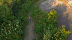 Tir aérien d'une jeune femme courant au territoire d'une vieille 1ère forteresse de guerre mondiale pendant le coucher du soleil, clips vidéos