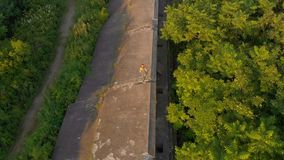 Tir aérien d'une jeune femme courant sur une vieille 1ère forteresse de guerre mondiale pendant le coucher du soleil, lever de so clips vidéos