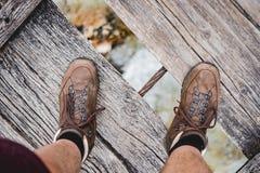 Tir aérien d'une position masculine de pieds sur un pont en bois portant augmentant des chaussures images libres de droits