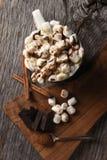 Tir aérien d'une tasse de cacao chaud avec les guimauves grillées à côté d'une planche à découper avec des gros morceaux de choco photos libres de droits