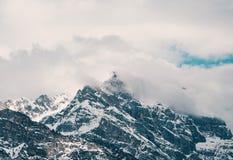 Tir aérien de belles montagnes neigeuses rocheuses couvertes en nuages photos libres de droits