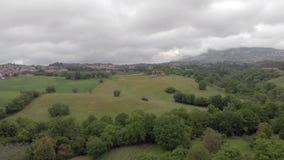 Tir aérien de campagne avec les collines vertes et forêts avec des horizons de village banque de vidéos