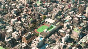 Tir aérien de champ de sports dans l'arbre de ciel de Tokyo montrant des enfants jouant sur un champ d'école clips vidéos