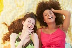 Tir aérien de deux amis féminins se trouvant sur le lit Image libre de droits