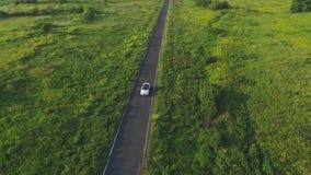 Tir aérien de l'équitation convertible blanche de voiture par la route rurale vide Quatre jeunes femmes méconnaissables voyageant clips vidéos