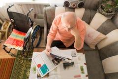 Tir aérien de la lecture de vieil homme au journal Photographie stock