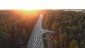 Tir aérien de lever de soleil de route en dehors de ville dans une forêt de campagne avec des cartes et camions passant l'achat - clips vidéos